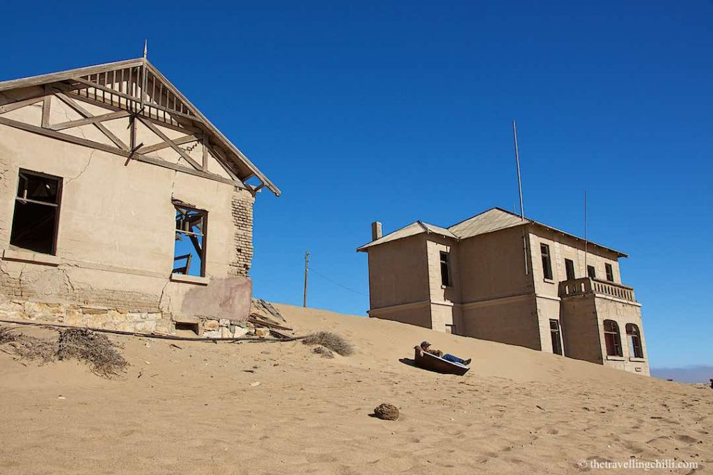 Two deserted houses in Kolmanskop ghost town in Namibia with a bath tub in the sand