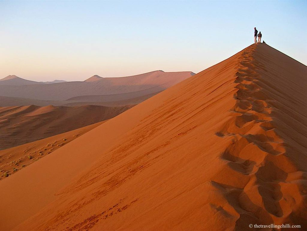 Dune 45 during sunrise with two people walking up the dune in Sossusvlei Namibia