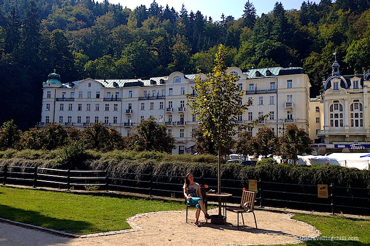wide angle view of the Grandhotel Pupp in Karlovy Vary with forest and mountains in the background