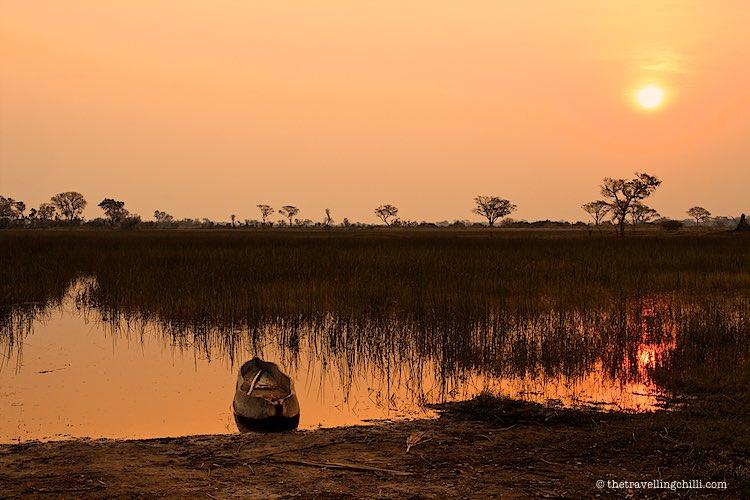 African sunset with mokoro Okavango Delta Botswana