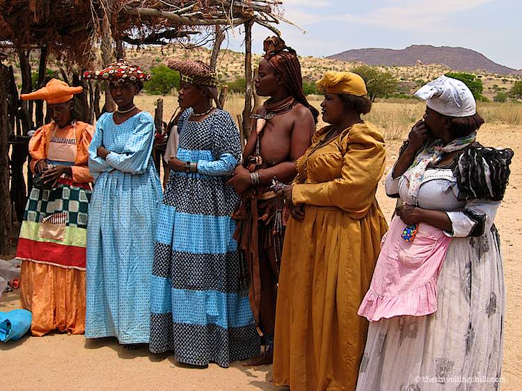 Herero woman with Victorian dresses and himba women selling handicrafts in namibia