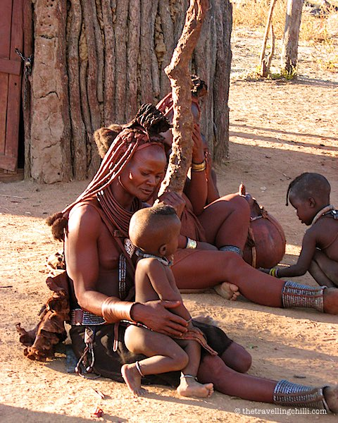 Himba child sitting on mothers lap in Himba village in Kamanjab Namibia