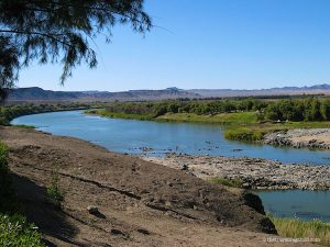 View of the Orange River or Gariep river in Namibia with blue water and desert mountains
