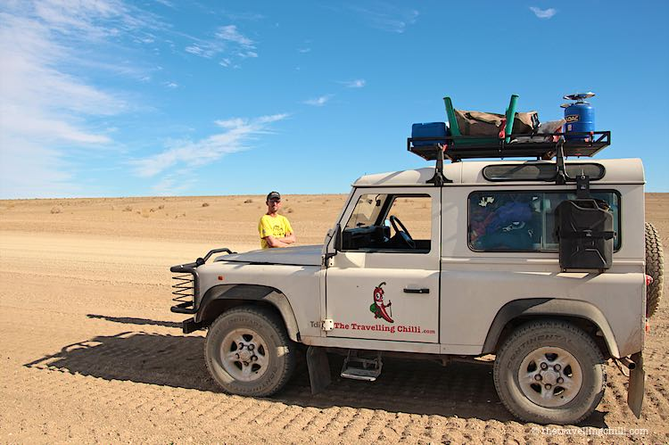 Driving in Namibia desert with white Landrover Defender 90