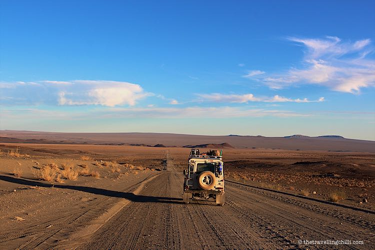 White Landrover Defender 90 driving on the Gravel roads in the desert of Namibia