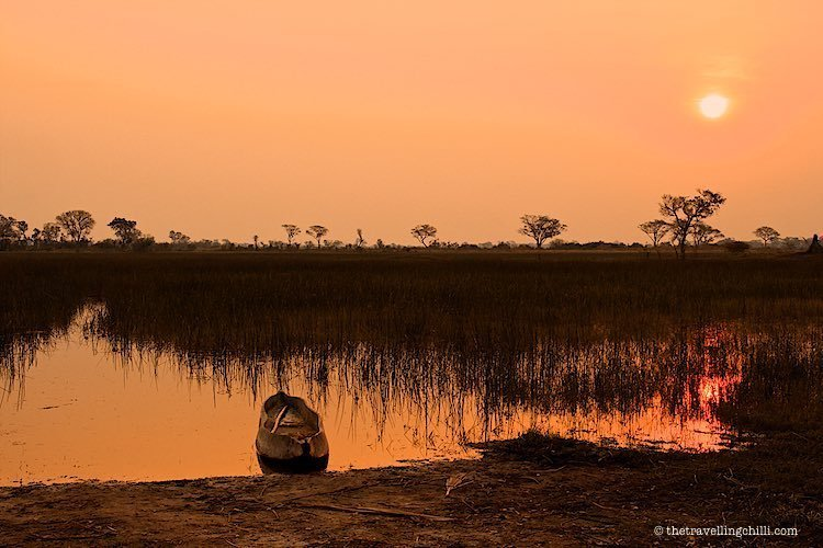 Golden hour Sunset with mokoro boat in the Okavango Delta in Botswana