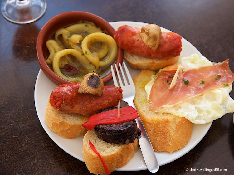 a plate of Spanish tapas with chorizo a la sidra, calamari and morcilla