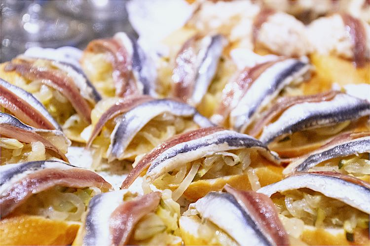 Pintxos or Pinchos are Spanish tapas eaten in the Basque Country like these slices of bread with anchovis