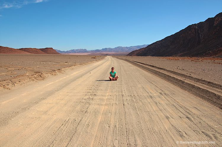 Sand road in the Namib desert leading to the Fish River Canyon Namibia with a person sitting on the road