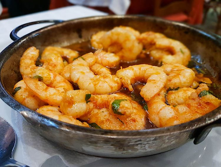 Gambas al pil pil is a Spanish dish made with shrimps, garlic and chilli and is a common Spanish tapa