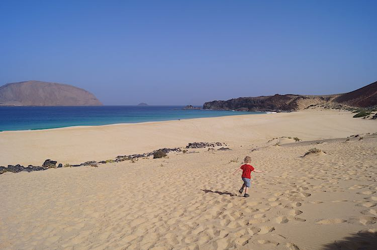 Child running on Playa de las Conchas in Lanzarote Spain