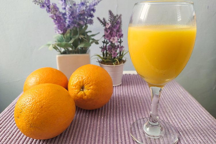Agua de Valencia in a wine glass with oranges and lavender flowers