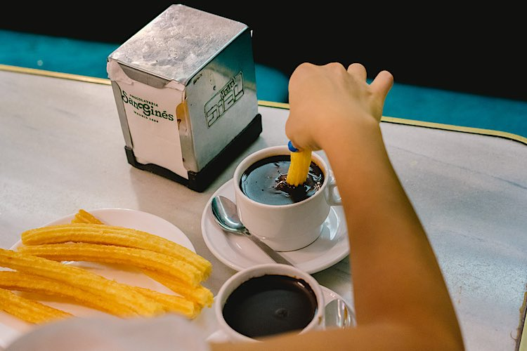 Person dipping churros in a cup of thick chocolate sauce
