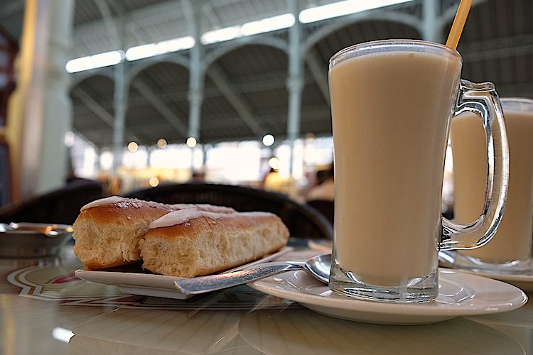 Glass of Horchata drink in Valencia with two pastries