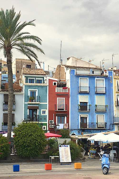 Painted houses in Vila Joiosa in blue and red with a palmtree