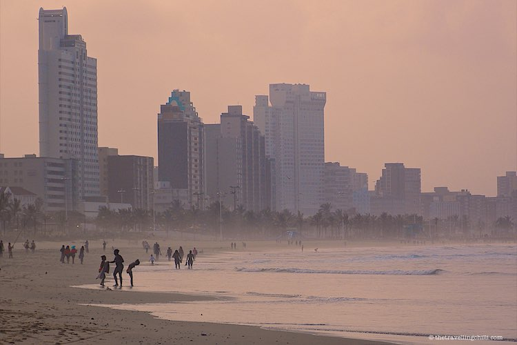 View of Durban skyline and Durban beachfront during the late afternoon light with people walking on the beach