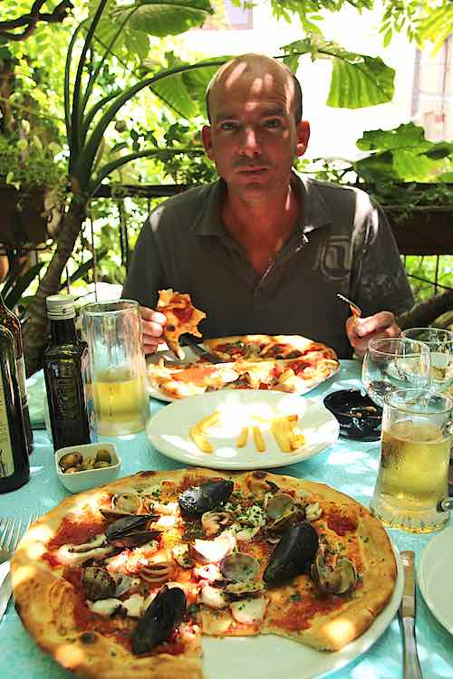 Eating Italian pizza in a pizzeria in Sorrento Italy | seafood pizza