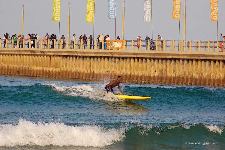 Man surfing by the Durban beach next to the Durban pier